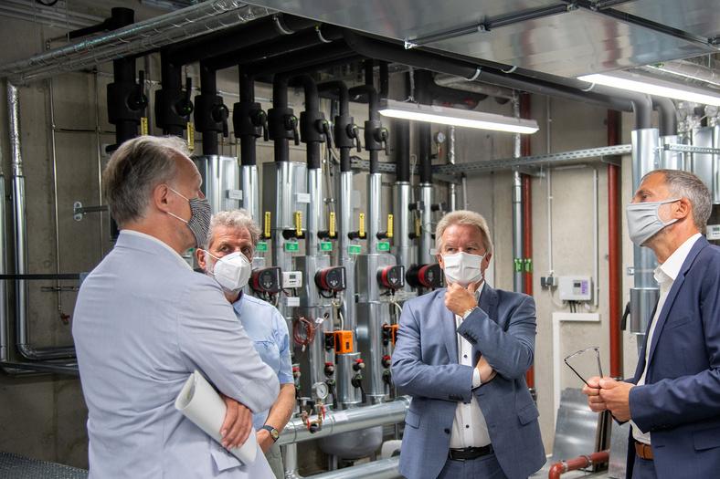 Umweltminister Untersteller steht mit drei weiteren Männern in Hallen des Stadtwerks von Leinfelden Echterdingen.