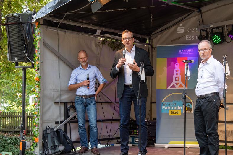 Während der Nachhaltigkeitstage in Kirchheim unter Teck stehen auf einer Bühne drei Männer, von welchen einer gerade einen Vortrag hält.