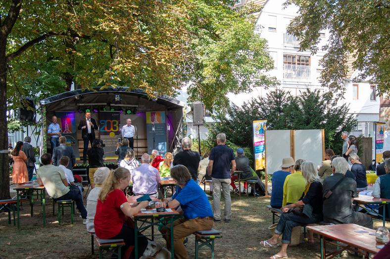 Bühne mit Sprechenden sowie Menschen davor, welche sich auf Bierbänken versammelt haben und dem Vortrag zuhören.