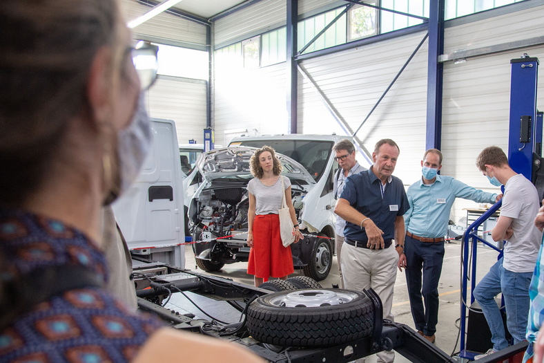 Während einer Führung durch die Firma EFA-S stehen eine Gruppe von Menschen um einen Transporter während ein Mann etwas erklärt.