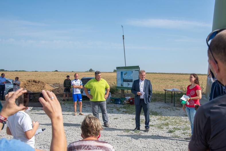 Eine gruppe von Menschen und Minister Untersteller haben sich vor dem Windkraftwerk in Ingersheimm versammelt.