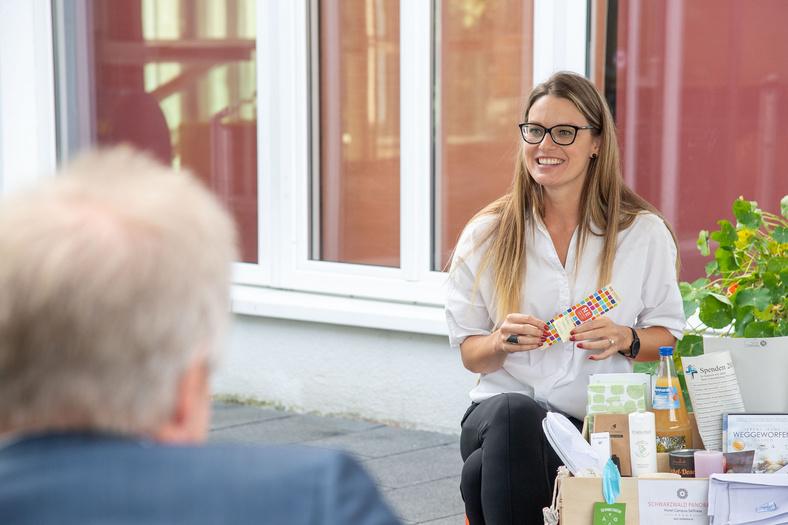 Mitarbeiterin des Hotels Schwarzwald Panorama hält Lesezeichen der Nachhaltigkeitsstrategie.